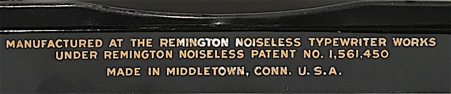Closeup of label on rear of machine. The white lettering is not an effect of lighting, but a slight discoloration of the lettering.